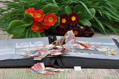 Stamp album with pile of stamps. Pile of stamps collection on opened album with colored natural background stock image