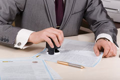 Stamp for imprinting on. A person at a desk using a stamp or corporate seal on documents stock image
