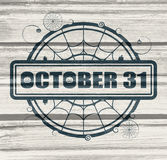 Stamp with October 31 text. And spider net. Round shape. Wood texture Stock Images