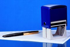 Stamp and pen - authentication of documents. Stamp — relief device for obtaining the same graphic prints of the name of stock photography
