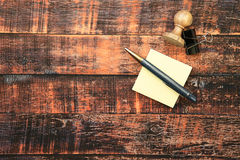 Stamp, pinch and pen with paper notes on wooden background Royalty Free Stock Photo