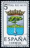 Stamp printed in Spain dedicated to Arms of Provincial Capitals shows Rio Muni. SPAIN - CIRCA 1965: A stamp printed in Spain dedicated to Arms of Provincial Royalty Free Stock Photo