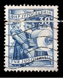 Stamp printed in Yugoslavia shows woman with books in publishing. A stamp printed in Yugoslavia shows woman with books in publishing, domestic economy Series Stock Photo