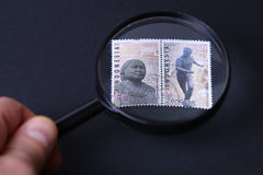 Stamp under magnifier Royalty Free Stock Photography