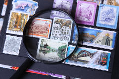 Stamp under magnifier. Postage stamp under magnifier on black background Stock Photo