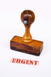 Stamp urgent. A photo of wooden stamp and urgent stamp  against white background Stock Photo