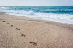 Stampa del piede sulla sabbia di Mar Nero Stampe della scarpa sulla spiaggia S Fotografie Stock