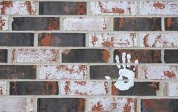 Stampa della mano sulla priorità bassa del mattone Fotografia Stock Libera da Diritti