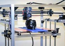 stampante 3D che stampa un modello sotto forma di primo piano nero del cranio Immagine Stock