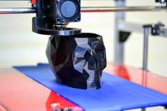 stampante 3D che stampa un modello sotto forma di primo piano nero del cranio Fotografia Stock