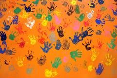 Stampe colorate della mano sulla parete arancione Immagini Stock