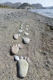 Stampe del piede delle pietre sulla spiaggia Lesvos Fotografia Stock