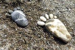 Stampe del piede delle pietre sulla spiaggia Lesvos Immagini Stock
