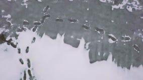 Stampe del piede e foro del ghiaccio su un lago video d archivio