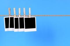 Stampe istantanee in bianco della foto su una corda Immagine Stock
