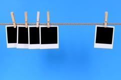 Stampe istantanee in bianco della foto su una corda Fotografia Stock