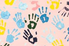 Stampe variopinte della mano sulla parete rosa Immagini Stock