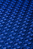 Stamped Metal Blue. Stamped metal with blue light on black glass. Geometric shapes with triangles. Great for industrial backgrounds royalty free stock photos