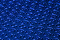 Stamped Metal Blue. Stamped metal with blue light on black glass. Geometric shapes with triangles. Great for industrial backgrounds stock photos