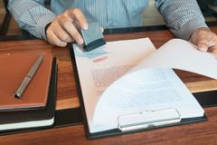 Stamper appoval da tinta da mão do notário de Hand do homem de negócios que carimba o selo em contrato aprovado dos documentos do foto de stock
