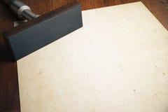 Stamper and paper sheet. Rectangular stamper and aged blank paper sheet on wooden desktop. Mock up, 3D Rendering Stock Photography