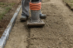 Stamping soil with rammer. To build the garden path Stock Image