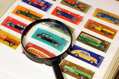 Stamps in an album and magnifying glass Royalty Free Stock Photos