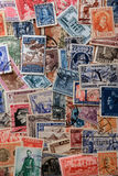 Stamps background. A background created with various used stamps from different countries (vertical stock photos