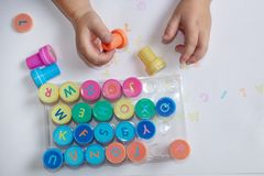 Stamps for children with the alphabet, children`s pens, play on paper. Childish games royalty free stock image