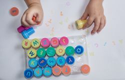 Stamps for children with the alphabet, children`s pens, play on paper. Childish games stock images