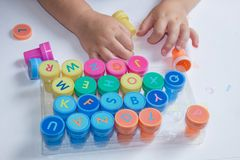 Stamps for children with the alphabet, children`s pens, play on paper. Childish games stock photography