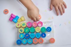 Stamps for children with the alphabet, children`s pens, play on paper. Educational games for children stock photography