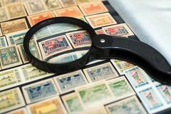 Stamps of the Republic of Azerbaijan in the book under a magnify. Old postage stamps with the image of a mosque in Azerbaijan stock photography