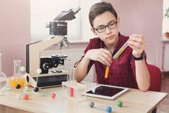 STAMutbildning Den tonårs- pojken gör kemisk forskning royaltyfri bild
