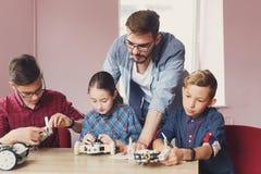 STAMutbildning Ungar som skapar robotar med läraren royaltyfria foton