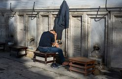 Stanbul, Turquia 10-November-2018 A lavagem muçulmana do homem fora da mesquita de Suleymaniye antes da manhã reza, Istambul foto de stock royalty free