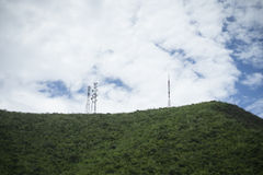 Stanchion of Telecommunication mast TV antennas wireless technology on a hilltop of green mountain, blue sky and cloud Stock Photo