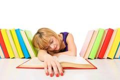 Stanco degli studi, giovane donna sta dormendo sul suo scrittorio con i libri Fotografia Stock