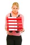 Stanco del gestore femminile del lavoro con il mucchio dei dispositivi di piegatura Fotografie Stock Libere da Diritti