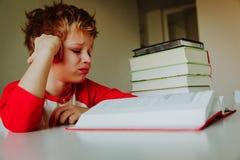 Stanco del ragazzino sollecitato di lettura, facendo compito Immagini Stock