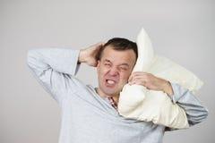 Stanco sonnolento dell'uomo con il cuscino su grey Fotografia Stock Libera da Diritti