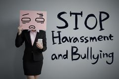 Stand against sexual harassment. Business woman take upset billboard and use smart phone with harassment concept  on the gray background Stock Images
