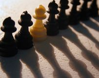 Stand Alone. Different - A single white pawn among black pawns. Shot against backlighting on Styrofoam board stock photography