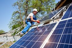 Stand-alone exterior solar panel system installation, renewable green energy generation concept. Young technician in protective helmet on tall metal platform royalty free stock image
