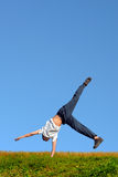 Stand on arm. Somersault on grass on the blue sky background Stock Image