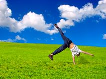 Stand on arm. Somersault on grass on the blue sky background Stock Images