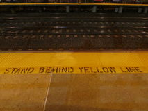 Stand behind yellow line sign and tracs at Edison train station late evening, NJ USA. Royalty Free Stock Photography