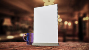 Stand for booklets white sheets of paper acrylic table. Stand for booklets with white sheets of paper acrylic table tent card mockup on wooden table with cup of Stock Image