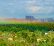 The Stand: City advance. The Stand near Moscow: Countryside, forest line, wall of rain and rainbow VS frontal attacking city. Village in focus, City - under rain Royalty Free Stock Images