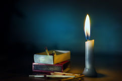 stand in dark candle lit with match box and sticks lying on floo Stock Photography